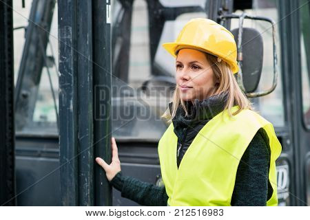 Female forklift truck driver outside a warehouse. A woman standing by the fork lift truck.