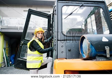 Female forklift truck driver outside a warehouse. A woman getting in the fork lift truck.