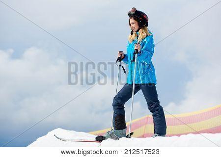 Beautiful Woman Skier Wearing Blue Ski Suit And Black Helmet, Enjoying Skiing At Ski Resort In The M