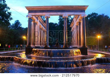 The fountain in the Park. Beautiful big fountain in the Park. Fountain with pillars and a waterfall in the Park. Walk through the night Park. The fountain in the Park in Petergof in Petersburg