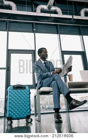 Middle aged African american Businessman reading newspaper in the airport