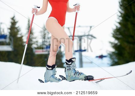 Close-up Girl's Legs With Boots, Skis. Skier Wearing Red Bodice, Holding Poles, Standing On Snowy Sl