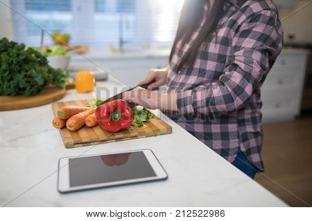 Mid section of pregnant woman chopping vegetables in kitchen