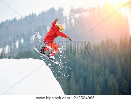 Male Snowboarder Freerider Jumping From The Top Of The Snowy Hill With Snowboard. Skiing And Snowboa