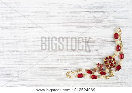 Woman's Jewelry. Vintage jewelry background. Beautiful bright rhinestone brooch and necklace on wood background. Flat lay top view with copy space