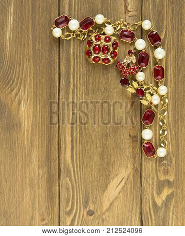 Woman's Jewelry. Vintage jewelry background. Beautiful bright rhinestone brooch and necklace on wood background. Flat lay top view.