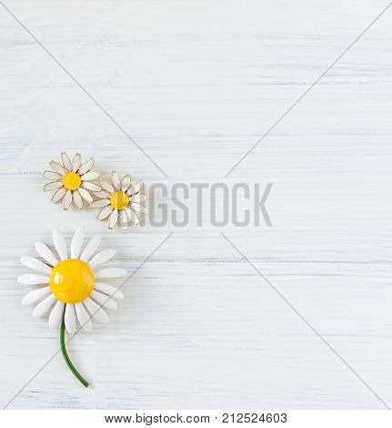 Woman's Jewellery. Vintage jewelry background. Beautiful daisy vintage brooch and earrings on white. Flat lay top view.