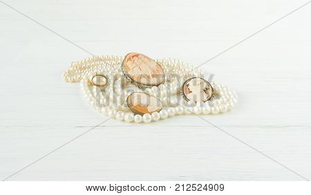 Woman's Jewelry. Vintage jewelry background. Beautiful pearl necklaces and cameo brooches. Flat lay top view.