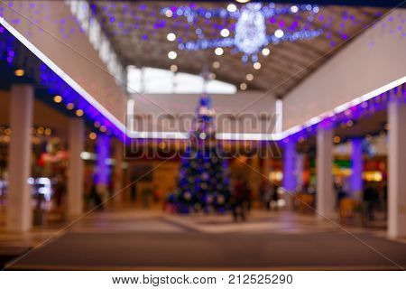 Giant Christmas tree in shopping mall. Blurred background. Christmas tree with gold decoration in shopping mall.clearance sales at the shopping mall. Elegant tree in a shopping mall