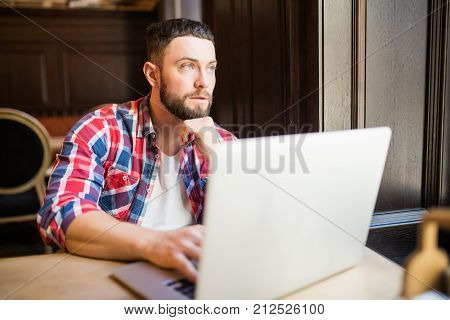 Smiling Man Using Laptop In Restaurant Working