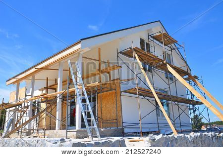Unfinished house. Home Remodeling and Renovation. Painting house wall with stucco and plastering. Insulation House Wall and Renovation.
