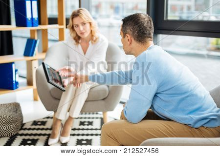 Explain me this. Smart pleasant handsome man sitting opposite his therapist and pointing at the tablet while asking to explain his diagnosis