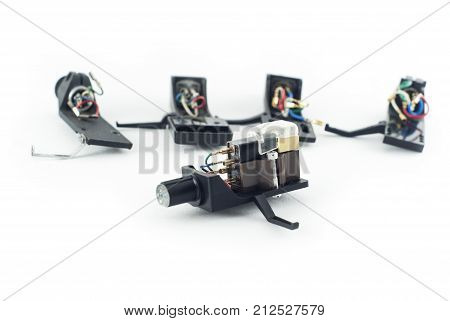 Moving magnet cartridge lying separately on a white background against the several different brackets-holders for such cartridge