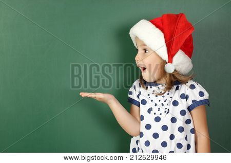 surprised child girl with santa hat holds his hand near empty school blackboard
