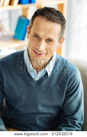 Positive emotions. Nice positive handsome man smiling and being in a good mood while looking at you