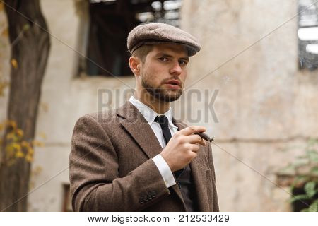 A young white man with a stubble in a suit and hat stands on the street and smokes a cigar. Retro. Outdoors.