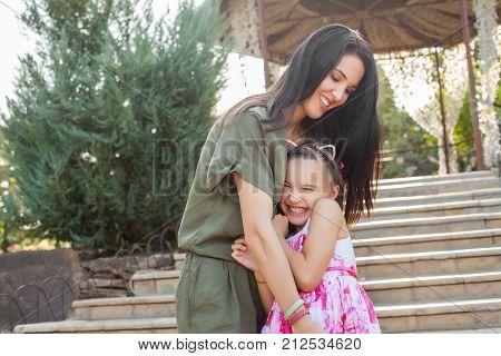 Beautiful mom and daughter playing on stairs in park, they hugging, smiling and having fun outdoos. Concept of happy family