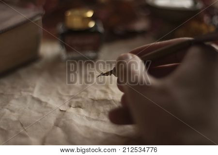 Old to do list paper with a writing hand with feather pen and ink and Bible on wooden table
