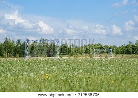 Horizontal shot of the village football field summer frame