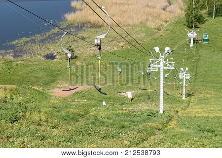 Horizontal shot of lifts for skiers over the lake and green field summer background. Transporting hikers in summer season.