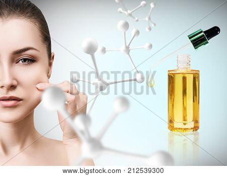 Cosmetic oil applying on woman face with pipette near big white molecule. Beauty therapy concept.