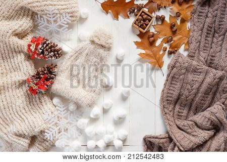 Autumn and winter stylish woman's outfit. Sweater, hat, shoes and small autumn related items, top view
