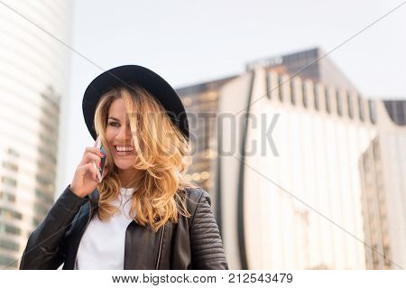 business communication. Girl in fashionable leather jacket with cell phone. communication business and new technology. woman with happy face in stylish hat speak on phone copy space