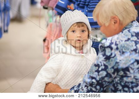 Adorable toddler girl and her grandmother in children apparel store buying clothes warm coat for cold weather.