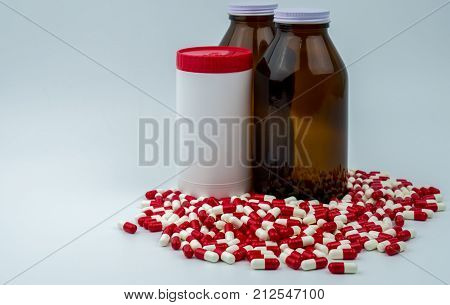 Colorful of antibiotic capsules pills with three bottles on white background. Drug resistance antibiotic drug use with reasonable health policy and health insurance concept.