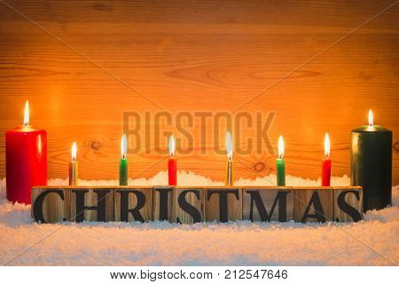 The word Christmas made from wooden letters in artificial snow with candles burning and a wooden background.