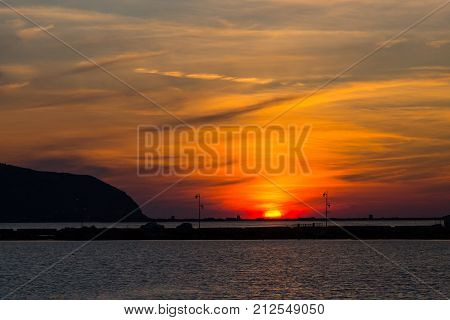 Sunset At Lefkas Lagoon In Greece With Dike, Water, Streetlamps