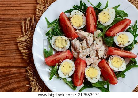 Vegetable salad with chicken breast and quail eggs. Salad with fresh tomatoes, rucola, quail eggs, boiled chicken breast and spices on a white plate and a wooden table. Closeup. Top view