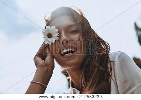 Playful girl. Low Angle view of attractive young smiling woman covering eye with chamomile and looking at camera while spending carefree time outdoors