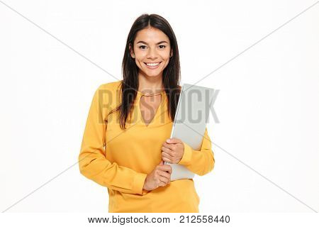 Portrait of a smiling successful woman holding laptop computer and looking at camera isolated over white background