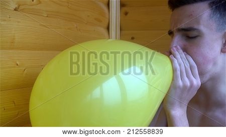 young man inflating yellow balloon, and then he explodes or bursts.