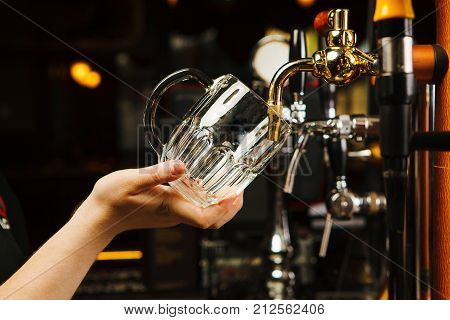 Barman going to pour beer into glass goblet from tap, closeup hands of male with transparent mug near bar counter with golden faucet