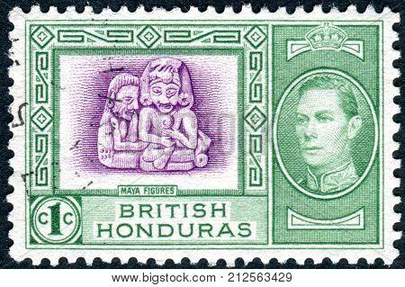 BRITISH HONDURAS - CIRCA 1938: Postage stamp printed in British Honduras shows Mayan Figures of Stann Creek and King George VI circa 1938