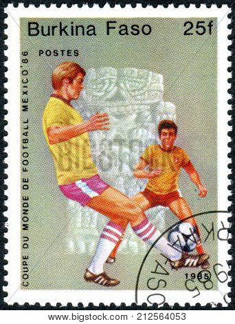 BURKINA FASO - CIRCA 1985: A stamp printed in Burkina Faso dedicated to FIFA World Cup in Mexico in 1986 shows the football players circa 1985