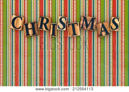 The word Christmas made from wooden letters on a striped festive background.