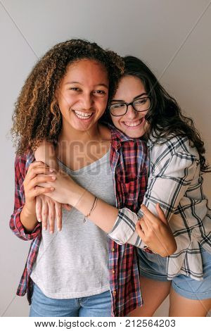Two teenage best friends girls hugging and smiling in a photoshoot