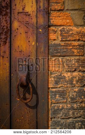 Rusty ring on iron plate next to an old brick wall