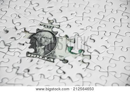 Missing jigsaw puzzle pieces on money dollar background Business solution concept key for success