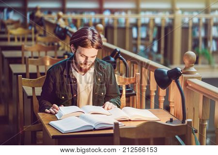 Young student man reading in a library hall on table with lot of books and lamp, indoor dusk time, education concept