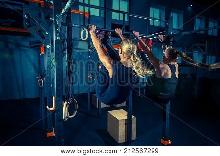 Concept: power, strength, healthy lifestyle, sport. Powerful attractive muscular women at crossfit gym during workout at the gym