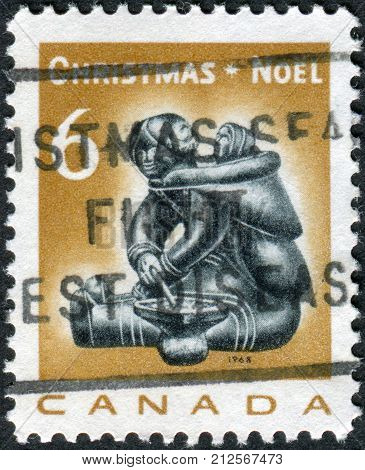 CANADA - CIRCA 1968: Postage stamp printed in Canada Christmas Issue shows Eskimo soapstone carving: Mother and infant by Munamee of Cape Dorset circa 1968