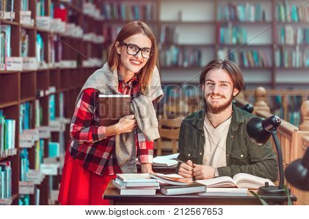 Portrait of two successful students casual stylish, boy and girl in library reading hall, evening time, education concept