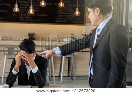 Businessman angry boss manager pointing his finger to underling man to complaint for project delay and unsuccessful while young businessman raise hands to close or cover his face.