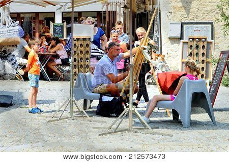 Carcassonne, Languedoc-roussillon, France - August 24 2017: Onlookers Watch As A Street Artist Draws