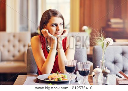 Picture showing bored Woman Alone at Restaurant