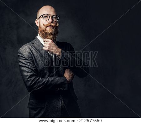 An elegant redhead bearded aristocratic male dressed in a suit and eyeglasses over grey background.
